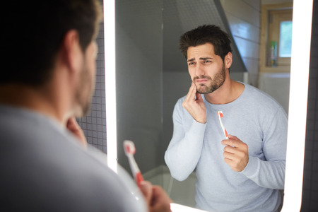 Sad frowning handsome brunette young man with beard touching cheek and looking into mirror in bathroom while getting bad tooth during cleaning teeth Фото со стока - 111137410