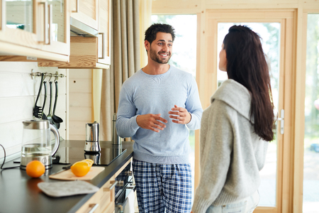 Cheerful handsome young bearded husband in pajamas standing in kitchen and gesturing hands while sharing story with wife, they preparing breakfast together 写真素材