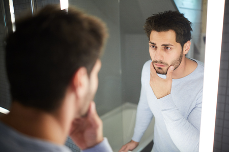 Serious handsome brunette young man touching beard and looking into mirror while thinking about shaving in bathroom
