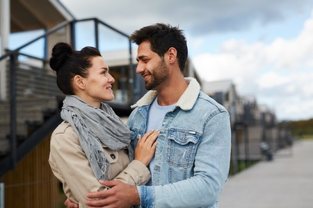 Happy beautiful young couple in love standing outdoors and hugging each other while looking into eyes