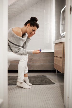 Upset shocked attractive young woman with hair bun sitting on toilet bowl in bathroom and looking at pregnancy test, she not believing her eyes Stock Photo