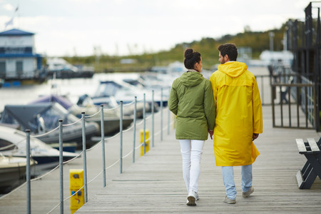 Rear view of young couple in coats holding hands and walking over pier together, they enjoying stroll on autumn day