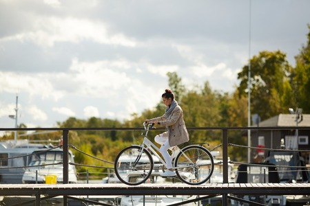 Serious concentrated young woman in coat riding bike carefully on pier and focused on motion while crossing pier alone