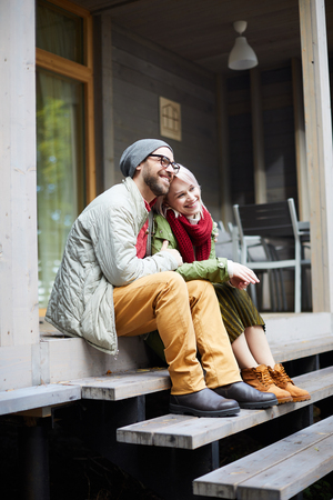 Young attractive fashionable Caucasian couple sitting on wooden steps of new house, embracing each other and smiling cheerfully Archivio Fotografico