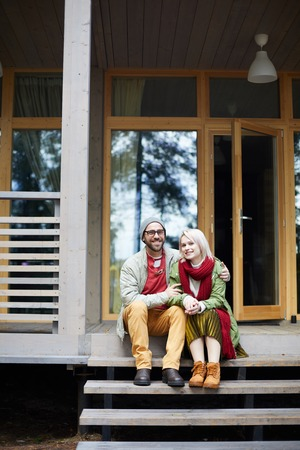 Portrait of young beautiful stylish Caucasian couple sitting on front stoop of new house and smiling at camera happily