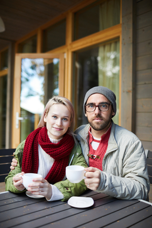 Portrait of young attractive Caucasian couple sitting at wooden table on terrace, holding cups of hot tea and looking at camera 免版税图像