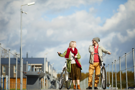 Young stylish Caucasian couple chatting and smiling happily while walking along the pier with bicycles on warm autumn afternoon, low angle view