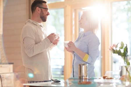 Young loving Caucasian couple drinking fresh coffee, chatting and smiling cheerfully while standing in cozy sunlit kitchen