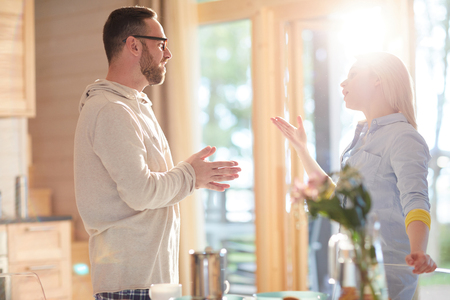 Young married Caucasian couple talking passionately while standing in home kitchen illuminated with bright morning sunlight Stock Photo