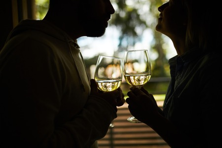 Silhouette of unrecognizable romantic couple holding glasses of white wine and  looking at each other with admiration Imagens - 111138216