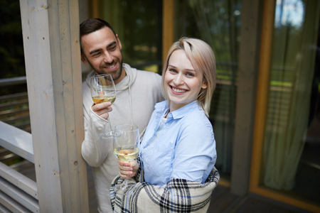 Portrait of young beautiful Caucasian woman standing on porch with glass of white wine and smiling at camera happily, her boyfriend looking at her with adoration