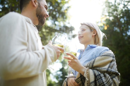Low angle view of young loving Caucasian couple clinking glasses of white wine outdoors and looking at each other with adoration Stock Photo