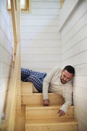 Young Caucasian man in homewear lying on wooden staircase at his house and wincing at pain after falling from high distance Banco de Imagens
