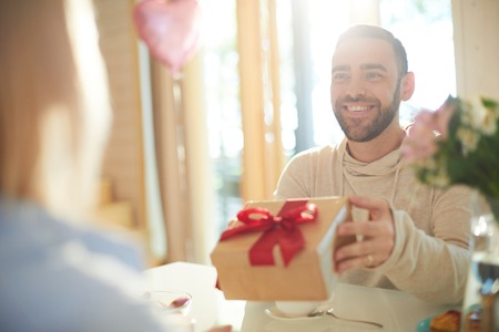 Young handsome bearded Caucasian man presenting gift to his girlfriend and smiling cheerfully while celebrating Valentines Day Imagens