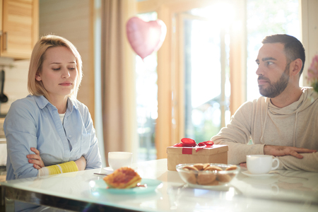 Young Caucasian woman looking at present box with disapproval while sitting at kitchen table with upset husband trying to make up