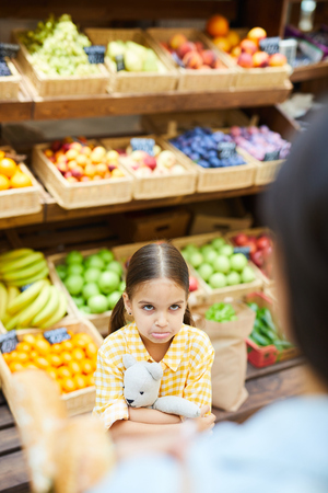 Resentful kid looking at parent in organic food store