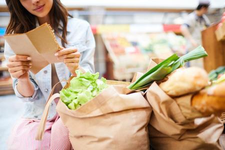Frau liest Einkaufsliste im Laden Standard-Bild