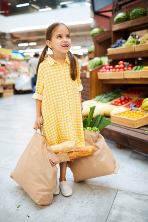 Excited girl carrying full shopping bags in farmers market