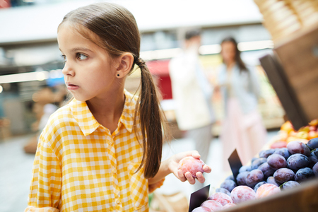 Worried girl stealing plums in food store Фото со стока - 112974334