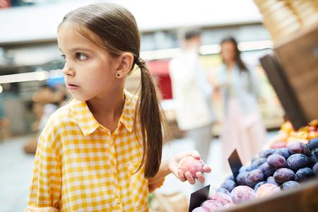 Worried girl stealing plums in food store 免版税图像 - 112974334