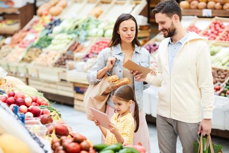 Modern family buying fresh organic food in farmers market