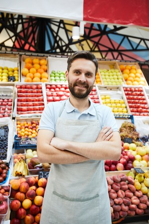 Content handsome retailer with beard against fresh food shelves 写真素材