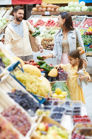 Positive family choosing fresh fruits and vegetables