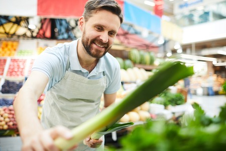 Handsome grocer in apron putting leeks on shelf