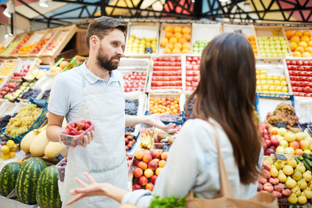 Confused grocer shrugging shoulders while talking to customer