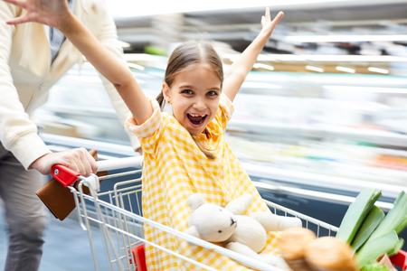 Excited girl riding in shopping cart Stock fotó - 112975386