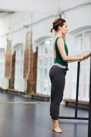 Girl training by gymnastic bar Фото со стока
