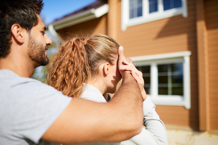 Young man covering eyes of his girlfriend by hand while both standing in front of their new house