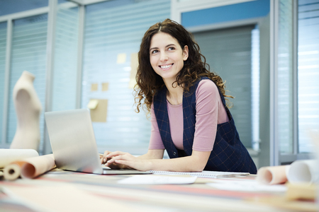 Smiling creative designer using laptop in tailoring studio