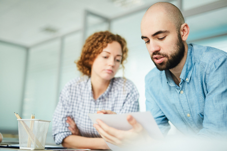 Bearded designer explaining his idea to colleague Stock Photo