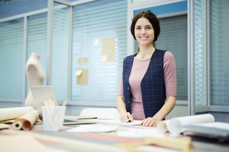 Cheerful lady in stylish waistcoat working in tailoring studio