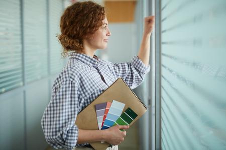 Smiling design student peeking through blinds