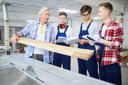Carpenter showing wooden plank to interns