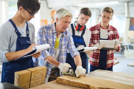 Professional carpenter explaining how to make wooden plank smoot Stock Photo - 113325618