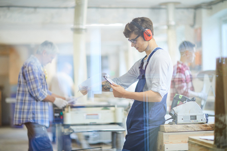 Busy young joiner reading operation manual in workshop Stock Photo