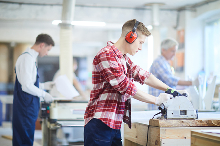 Concentrated carpenter in ear protectors working with circular s