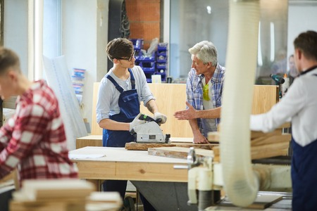 Senior carpenter teaching young worker at factory Stock Photo - 113325966