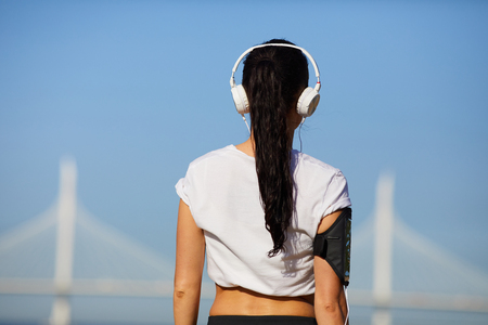 Athletic lady in headphones outdoors