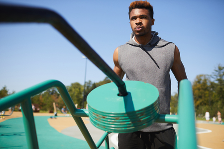 Black man breathing out while training with workout equipment Stock fotó