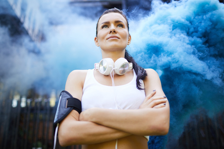 Content young woman standing in blue smoke