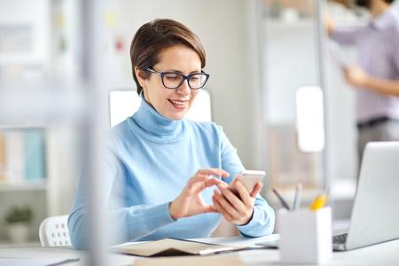 Texting by workplace Reklamní fotografie