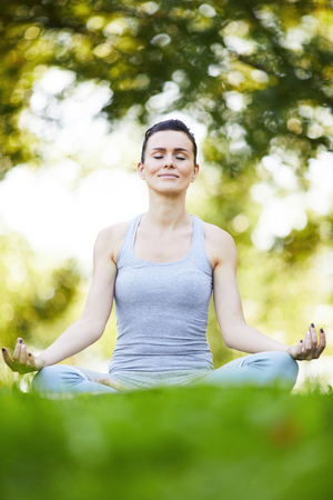 Lady meditating in lotus position outdoors