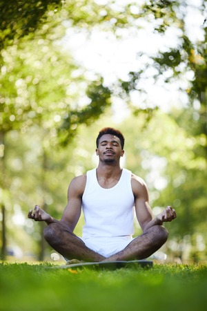 Serious black man with crossed legs meditating in park 스톡 콘텐츠