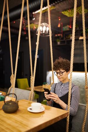 Texting in cafe Reklamní fotografie - 117433692