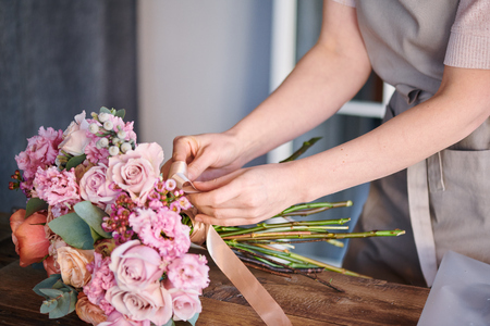 Tying bouquet with silk ribbon Stock Photo