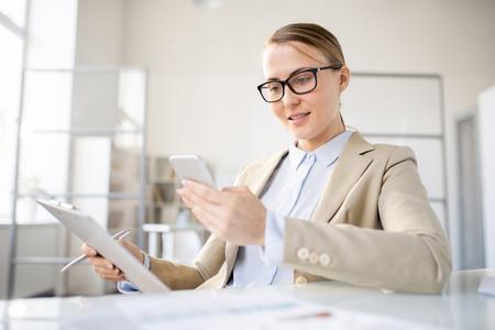 Smiling lady checking message on smartphone 版權商用圖片